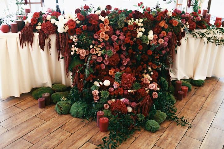 przyjęcie weselne dekoracja bordowe kwiaty ciemna zieleń świece
