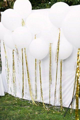 Białe balony ze złotymi wstęgami na weselu