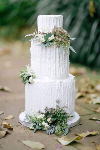 Biały tort weselny z zielonymi roślinami