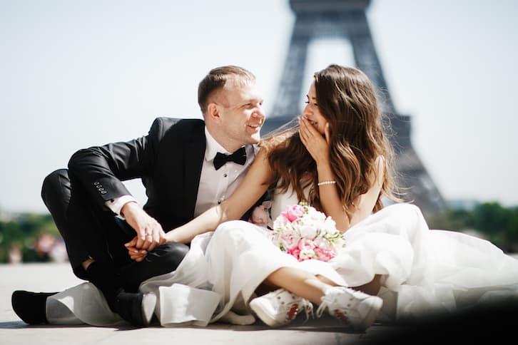 młoda para siedzi przed wieżą Eiffel'a