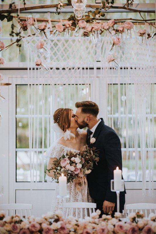 pierwszy pocałunek młodej pary na sali weselnej