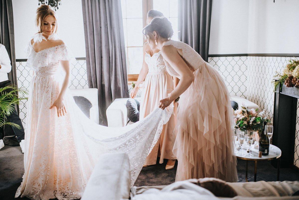 druhny pomagają pannie młodej z suknią