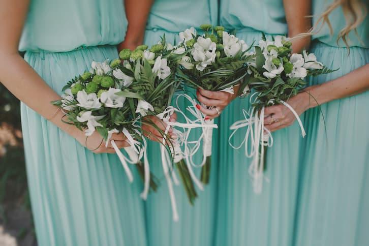 druhny w błękitnych sukniach trzymają kwiaty